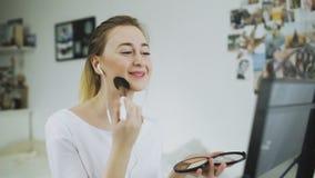 Η γυναίκα με το πρόσωπο ομορφιάς που εφαρμόζει Makeup και ακούει μουσική απόθεμα βίντεο