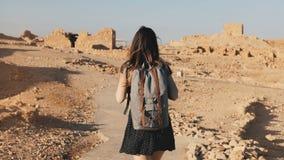 Η γυναίκα με το σακίδιο πλάτης ερευνά τις αρχαίες καταστροφές ερήμων Όμορφοι ευρωπαϊκοί περίπατοι τουριστών στους βράχους και την φιλμ μικρού μήκους