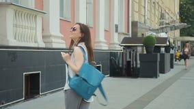 Η γυναίκα με το σακίδιο πλάτης στα γυαλιά ηλίου είναι ευτυχής περπατώντας στην πόλη απόθεμα βίντεο