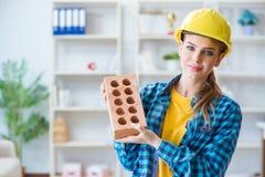 Η γυναίκα με το τούβλο στην έννοια κατασκευής Στοκ Εικόνες