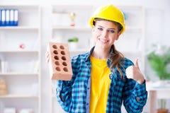 Η γυναίκα με το τούβλο στην έννοια κατασκευής Στοκ Φωτογραφίες