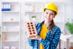 Η γυναίκα με το τούβλο στην έννοια κατασκευής Στοκ Φωτογραφία