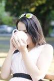 Η γυναίκα με το φλιτζάνι του καφέ σε ένα πάρκο και το πίνει Στοκ Φωτογραφίες