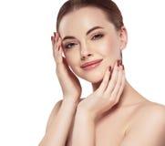 Η γυναίκα με το όμορφο πρόσωπο, το υγιές δέρμα και η τρίχα της σε μια πλάτη σχετικά με το πρόσωπό της με τα δάχτυλα κλείνουν επάν Στοκ Εικόνες