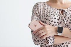Η γυναίκα με το iPhone 6 S εκμετάλλευσης ρολογιών της Apple αυξήθηκε χρυσός Στοκ Εικόνα