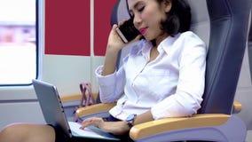 Η γυναίκα με το lap-top μιλά στο κινητό τηλέφωνο στο τραίνο φιλμ μικρού μήκους