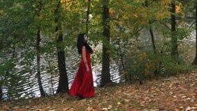 Η γυναίκα με τρομακτικές αποκριές αποτελεί στο κόκκινο φόρεμα περπατώντας στο δασικό πάρκο τα δέντρα απόθεμα βίντεο