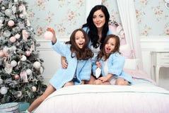 Η γυναίκα με δύο παιδιά στο μπλε πλέκει τη ζακέτα στο κρεβάτι κοντά στο χριστουγεννιάτικο δέντρο Στοκ Φωτογραφία