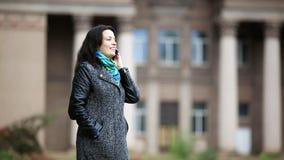 Η γυναίκα μιλά το τηλέφωνο και το χαμόγελο ευτυχώς στο πάρκο φθινοπώρου απόθεμα βίντεο