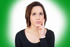 Η γυναίκα μπροστά από ένα πράσινο υπόβαθρο σκέφτεται Στοκ Εικόνες