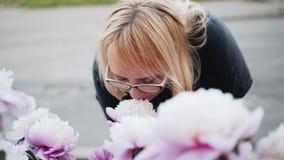 Η γυναίκα μυρίζει τα λουλούδια στο πάρκο φιλμ μικρού μήκους