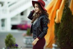 Η γυναίκα μόδας φορά τα θερμά ενδύματα και το καπέλο φθινοπώρου μόδας στο μπροστινό περπάτημα στο κέντρο πόλεων Στοκ Εικόνες