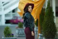 Η γυναίκα μόδας φορά τα θερμά ενδύματα και το καπέλο φθινοπώρου μόδας στο μπροστινό περπάτημα στο κέντρο πόλεων Στοκ εικόνα με δικαίωμα ελεύθερης χρήσης