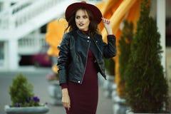 Η γυναίκα μόδας φορά τα θερμά ενδύματα και το καπέλο φθινοπώρου μόδας στο μπροστινό περπάτημα στο κέντρο πόλεων, αστικό ύφος Στοκ Φωτογραφία