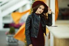 Η γυναίκα μόδας φορά τα θερμά ενδύματα και το καπέλο φθινοπώρου μόδας στο μπροστινό περπάτημα στην πόλη Στοκ Εικόνα