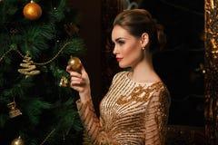 Η γυναίκα μόδας κρέμασε ένα παιχνίδι στο χριστουγεννιάτικο δέντρο στοκ εικόνες με δικαίωμα ελεύθερης χρήσης