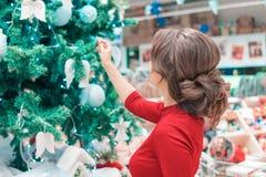 Η γυναίκα ντύνει ένα χριστουγεννιάτικο δέντρο με τα παιχνίδια δημιουργία μιας νέας διάθεσης έτους ` s Στοκ Φωτογραφία