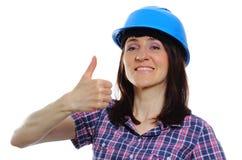 Η γυναίκα οικοδόμων στην παρουσίαση μπλε κρανών φυλλομετρεί επάνω Στοκ φωτογραφία με δικαίωμα ελεύθερης χρήσης