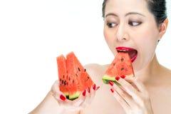 Η γυναίκα ομορφιάς απολαμβάνει το καρπούζι με τα κόκκινα χείλια, άπληστα, δάγκωμα Στοκ εικόνες με δικαίωμα ελεύθερης χρήσης