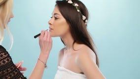 Η γυναίκα ομορφιάς κάνει το makeup της απόθεμα βίντεο