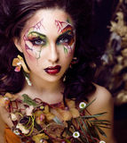 Η γυναίκα ομορφιάς με την τέχνη προσώπου και το κόσμημα από τις ορχιδέες λουλουδιών κλείνουν επάνω, δημιουργικό υπόβαθρο σχεδίων  Στοκ Φωτογραφία