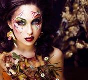 Η γυναίκα ομορφιάς με την τέχνη προσώπου και το κόσμημα από τις ορχιδέες λουλουδιών κλείνουν επάνω Στοκ εικόνα με δικαίωμα ελεύθερης χρήσης