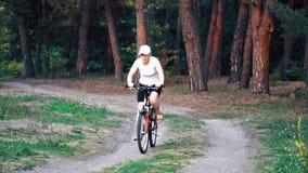 Η γυναίκα οδηγά ένα ποδήλατο μέσω του δάσους φιλμ μικρού μήκους