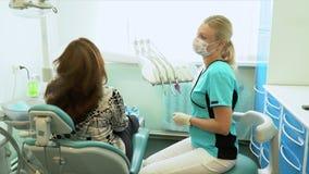 Η γυναίκα ο οδοντίατρος έχει σταματήσει τη μεταχείρηση και αφαιρεί ένα μίας χρήσης μαντίλι από τον ασθενή απόθεμα βίντεο