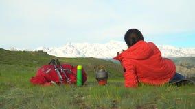 Η γυναίκα ο ταξιδιώτης με ένα κόκκινο σακίδιο πλάτης αυξάνεται από το βουνό Η γυναίκα κάθεται, εξετάζει τα βουνά χιονιού, στο αέρ απόθεμα βίντεο