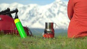 Η γυναίκα ο ταξιδιώτης με ένα κόκκινο σακίδιο πλάτης αυξάνεται από το βουνό Η γυναίκα κάθεται, εξετάζει τα βουνά χιονιού, στο αέρ φιλμ μικρού μήκους