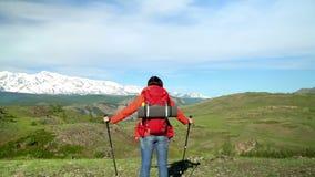 Η γυναίκα ο ταξιδιώτης με ανόδους τις κόκκινες σακιδίων πλάτης από το βουνό, εξετάζει τα βουνά χιονιού Σε αργή κίνηση πυροβολισμό φιλμ μικρού μήκους