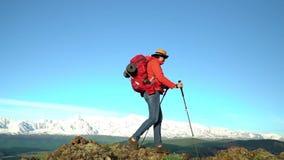 Η γυναίκα ο ταξιδιώτης με ανόδους τις κόκκινες σακιδίων πλάτης από το βουνό, εξετάζει τα βουνά χιονιού Σε αργή κίνηση πυροβολισμό απόθεμα βίντεο