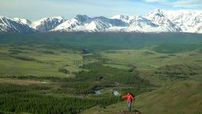Η γυναίκα ο ταξιδιώτης με ανόδους τις κόκκινες σακιδίων πλάτης από το βουνό, εξετάζει τα βουνά χιονιού απόθεμα βίντεο