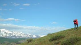 Η γυναίκα ο ταξιδιώτης με ανόδους τις κόκκινες σακιδίων πλάτης από το βουνό, εξετάζει τα βουνά χιονιού φιλμ μικρού μήκους