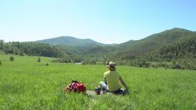 Η γυναίκα ο ταξιδιώτης με τα ραβδιά τουριστών και με ένα κόκκινο σακίδιο πλάτης αναρριχείται κάτω από ένα πράσινο βουνό Κατόπιν η φιλμ μικρού μήκους