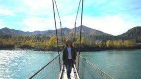 Η γυναίκα ο ταξιδιώτης πηγαίνει ο ιερέας στη γέφυρα αναστολής του ποταμού βουνών Βουνό Altai απόθεμα βίντεο