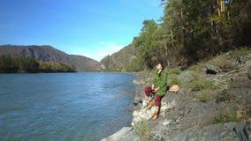 Η γυναίκα ο ταξιδιώτης στις όχθεις του ποταμού βουνών Βουνό Altai φιλμ μικρού μήκους