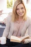 Η γυναίκα πίνει διαβάζοντας το βιβλίο Στοκ Εικόνες
