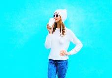 η γυναίκα πίνει τον καφέ στο άσπρο πουλόβερ, καπέλο σε ένα μπλε υπόβαθρο Στοκ φωτογραφία με δικαίωμα ελεύθερης χρήσης
