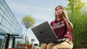 Η γυναίκα πίνει τον καφέ όπως εργαζόμενος απόθεμα βίντεο