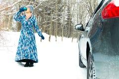 Η γυναίκα πίνει το θερμαίνοντας ποτό κοντά στο αυτοκίνητο το χειμώνα διάστημα αντιγράφων στοκ εικόνες