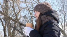 Η γυναίκα πίνει το καυτό τσάι ή τον καφέ από ένα άνετο φλυτζάνι στο χιονώδες χειμερινό πρωί υπαίθρια Όμορφο κορίτσι που απολαμβάν απόθεμα βίντεο