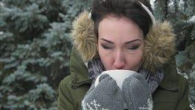 Η γυναίκα πίνει το καυτό τσάι ή coffe στο χειμερινό δάσος που είναι ντυμένη στα καλύμματα αυτιών γουνών στο κεφάλι της Όμορφο τοπ φιλμ μικρού μήκους