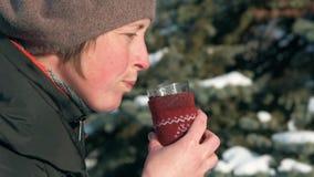 Η γυναίκα πίνει το καυτό τσάι στο δασικό, όμορφο χειμερινό τοπίο με τα χιονώδη δέντρα έλατου φιλμ μικρού μήκους