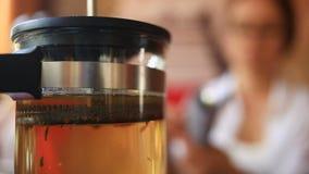 Η γυναίκα πίνει το πράσινο τσάι από teapot διαφανές Οι φίλοι τρώνε τα κινεζικά τρόφιμα σε ένα κινεζικό εστιατόριο φιλμ μικρού μήκους