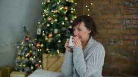 Η γυναίκα πίνει το τσάι κοντά στο χριστουγεννιάτικο δέντρο απόθεμα βίντεο