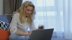 Η γυναίκα πίνει το τσάι κοντά στο lap-top στο σπίτι φιλμ μικρού μήκους