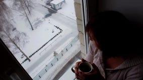 Η γυναίκα πίνει το χειμώνα παραθύρων καφέ απόθεμα βίντεο