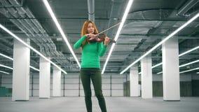 Η γυναίκα παίζει το βιολί στη μονάδα αποθήκευσης απόθεμα βίντεο