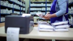 Η γυναίκα παίρνει από το κιβώτιο με το ύφασμα συσκευασίας φιλμ μικρού μήκους